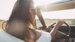 CU Carefree young woman driving convertible along sunny, rural fields