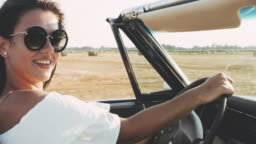 MS Carefree young woman driving convertible along sunny, rural fields