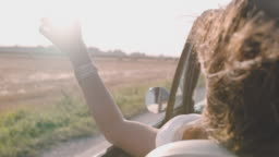 CU SLO MO Carefree young woman driving convertible along sunny, rural road