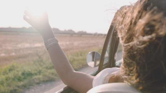 cu slo mo carefree young woman driving convertible along sunny, rural road - auto convertibile video stock e b–roll