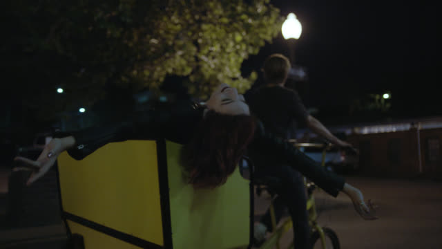 ws slo mo. carefree young woman hangs out of bike taxi on late night city ride. - 30 34 jahre stock-videos und b-roll-filmmaterial