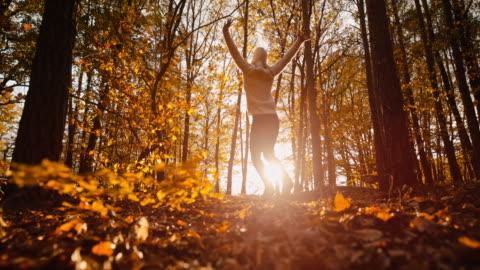 stockvideo's en b-roll-footage met ms super slow motion zorgeloze jonge vrouw die van vreugde springt in zonnige, idyllische herfstbossen - autumn