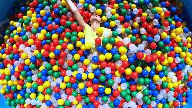 vídeos de stock, filmes e b-roll de carefree young woman playing in multicolor ball pool - jovem de espírito