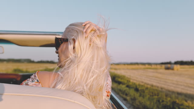 slo mo - time warp effect carefree young woman riding in convertible along sunny, rural field - convertible stock videos & royalty-free footage