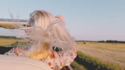 MS SLO MO Carefree young woman riding in convertible along sunny, rural fields