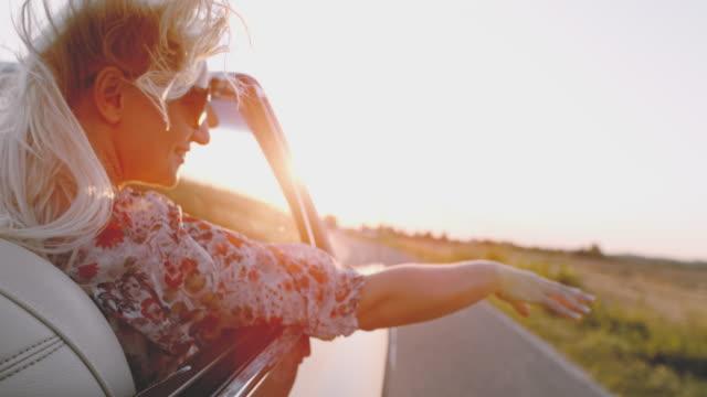 slo mo - time warp effect unbeschwerte junge frau reitet im cabrio auf sonniger landstraße - 25 29 jahre stock-videos und b-roll-filmmaterial