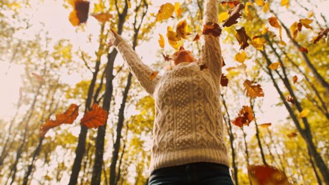 stockvideo's en b-roll-footage met ms super slow motion zorgeloze jonge vrouw spinnen in vallende gouden herfstbladeren in bos - muts