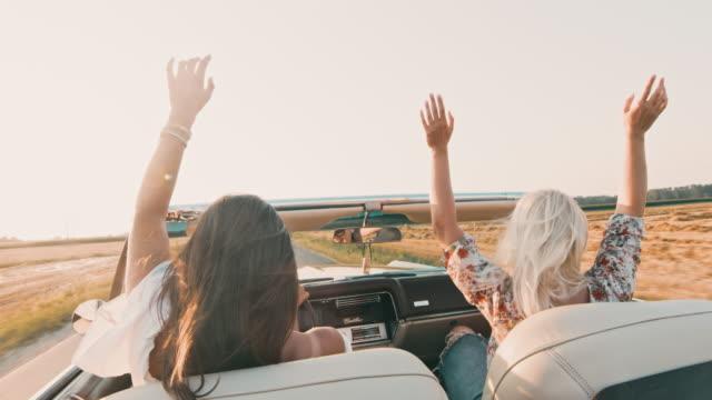 vídeos de stock, filmes e b-roll de mulheres novas de ms carefree que conduzem convertíveis ao longo da estrada ensolarada, rural - conversível