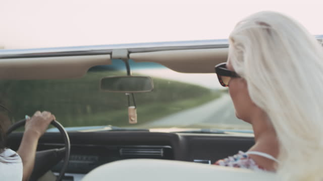 vídeos de stock, filmes e b-roll de mulheres novas de ms carefree que conduzem convertíveis na estrada rural - conversível