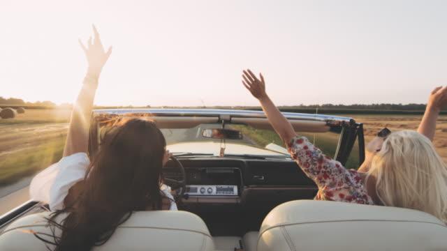 vidéos et rushes de ms carefree jeunes femmes conduisant décapotable sur le soleil, route rurale - voiture particulière