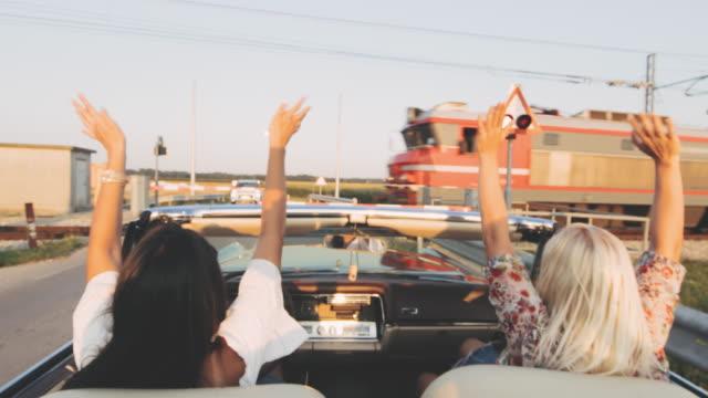 vídeos de stock, filmes e b-roll de mulheres novas de ms carefree no convertible que acena em passar o trem na estrada ensolarada, rural - conversível