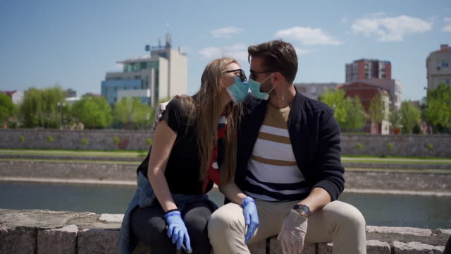 vídeos de stock e filmes b-roll de careful millennial couple trying to kiss while wearing protective face mask - higiene