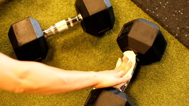 vídeos de stock, filmes e b-roll de limpeza cuidadosa dos pesos após o uso - equipamento para exercícios