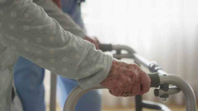 caregiver assisting old woman in walking at home - walking frame stock videos & royalty-free footage