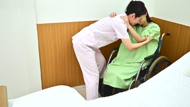 vårdgivare ta hand om en sjukhuskvinna - bära bildbanksvideor och videomaterial från bakom kulisserna