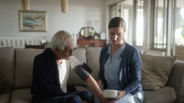 caregiver checking blood pressure of elderly man - female nurse stock videos & royalty-free footage