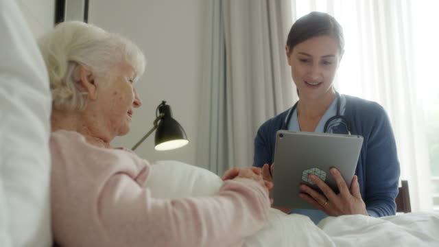 caregiver discussing medical record with old woman - medical record stock videos & royalty-free footage