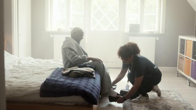 caregiver helping senior man to put on shoe - bathrobe stock videos & royalty-free footage