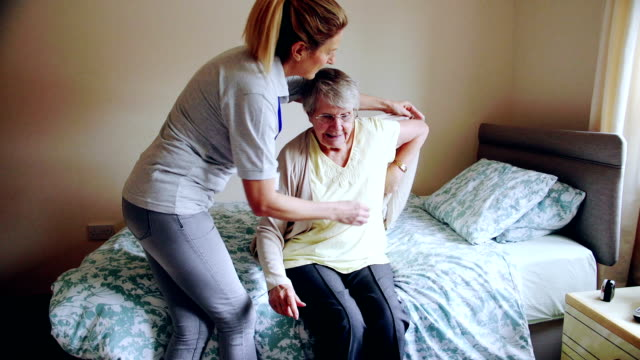 caregiver helping senior woman dress - terza età video stock e b–roll