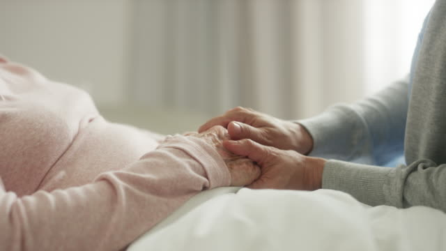 caregiver holding hands of senior patient - female nurse stock videos & royalty-free footage