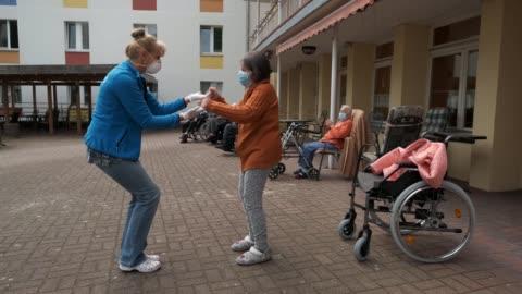 vídeos y material grabado en eventos de stock de caregiver marine lehmberg dances with resident marlene schulz who has dementia, at the hermann radtke haus nursing home during the novel coronavirus... - demencia