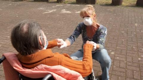 vídeos y material grabado en eventos de stock de caregiver marine lehmberg holds hands with resident marlene schulz who has dementia, at the hermann radtke haus nursing home during the novel... - demencia