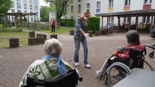 caregiver marine lehmberg wears a protective face mask and gloves as she dances in front of marlene schulz who has dementia, to a singer's live... - gesangskunst stock-videos und b-roll-filmmaterial