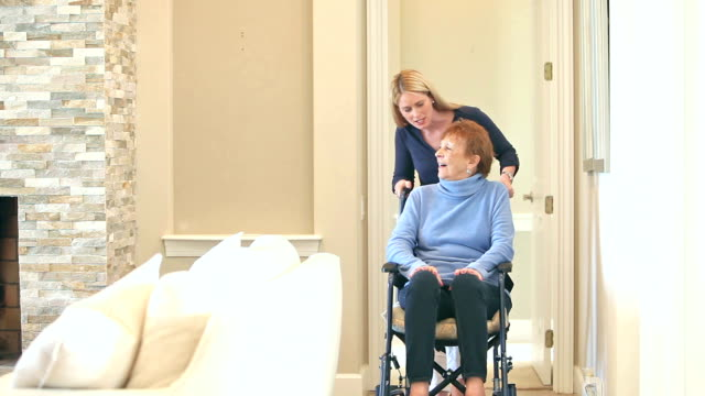 Caregiver pushing senior woman in wheelchair at home