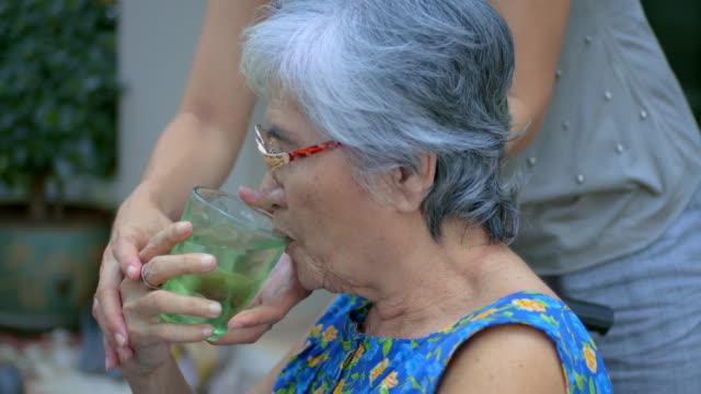 vídeos de stock, filmes e b-roll de o cuidador toma a mulher idosa do cuidado para a água bebendo. - doença
