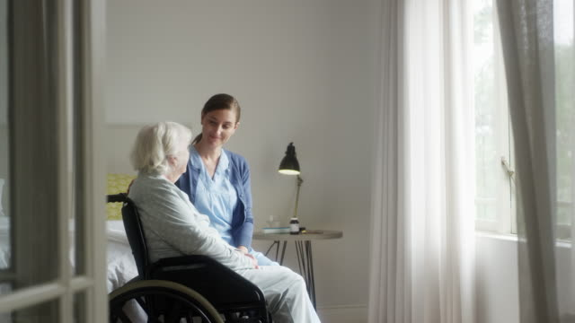 caregiver talking with woman sitting on wheelchair - dolly shot stock videos & royalty-free footage