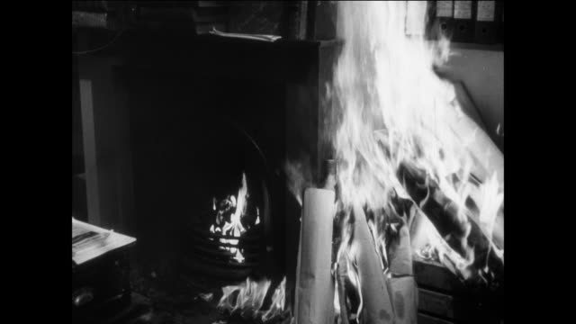 MONTAGE carelessness by people leads to home fires / UK / Wife opens door / wife looks a flames and turns away / fire burns rolls of paper / husband scatters fire to floor / wife yells into phone / boy opens door / children run out of room / baby watches