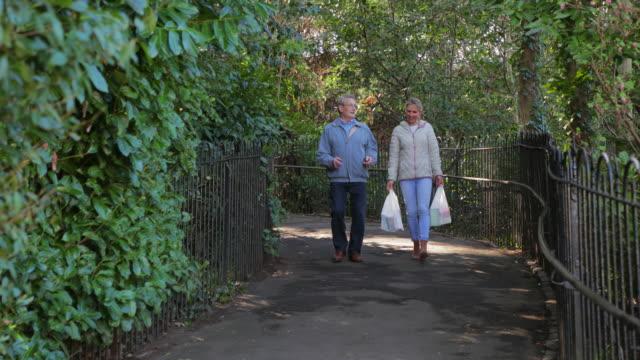 vidéos et rushes de soignant, porter les sacs tout en marchant la maison avec un homme senior - retraite