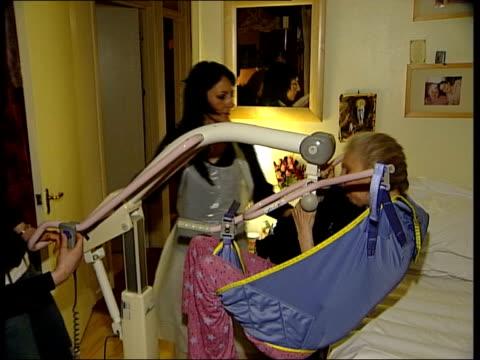 stockvideo's en b-roll-footage met carers in the community wright helping maryann lift carmel into bed using hoist carmel in bed maryann bidding her mum goodnight sot - hijsen
