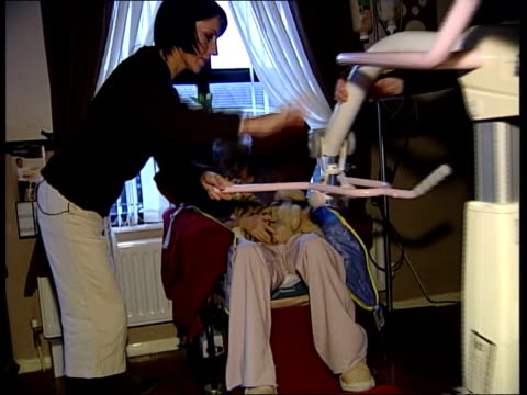 stockvideo's en b-roll-footage met carers in the community wright with maryann as carmel is lifted into armchair using hoist carmel sitting in armchair holding soft toy maryann... - hijsen