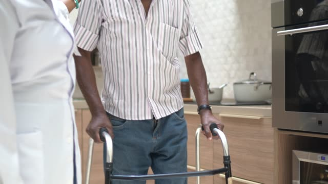 caretaker assisting senior man with walker - physical therapist stock videos & royalty-free footage