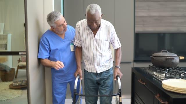 vidéos et rushes de gardien aidant l'homme aîné avec le marcheur - infirmier