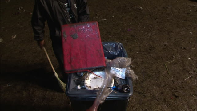 A caretaker dumps litter into a trash can.