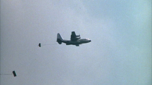 1967 ws ts cargo aircraft dropping down parachutes with supplies - cargo aeroplane stock videos & royalty-free footage
