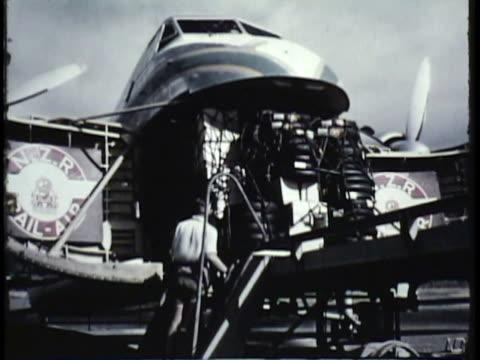 stockvideo's en b-roll-footage met 1955 montage ws ms tu la cargo being loaded into airplane, people boarding plane on airfield / new zealand / audio - 1955