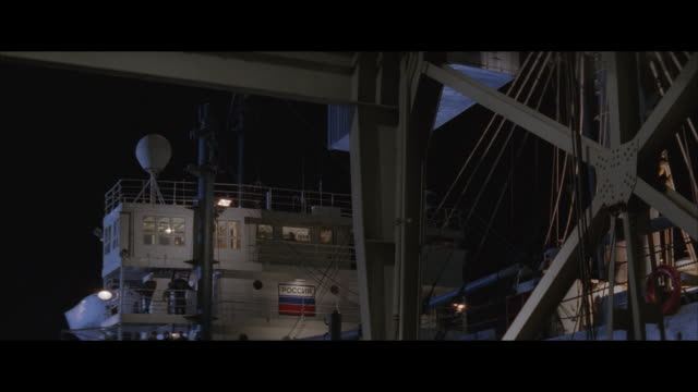 ms, pan, cargo container being loaded onto ship in dock at night - dockarbeiter stock-videos und b-roll-filmmaterial