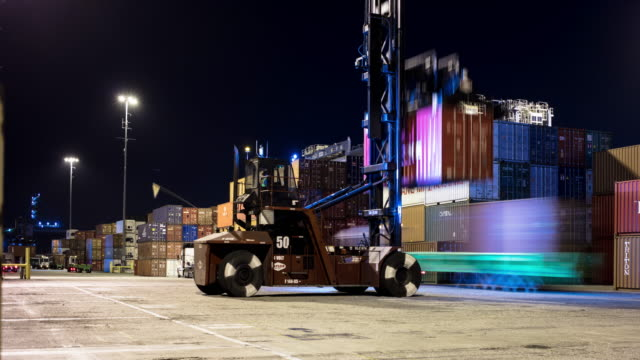 cargo container being organized in shipping terminal at night - time lapse - lastzug stock-videos und b-roll-filmmaterial