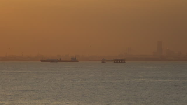 cargo container ship sailing at dusk