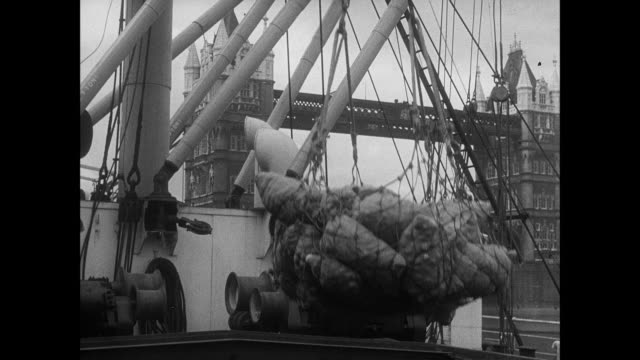 vídeos de stock e filmes b-roll de montage cargo is unloaded at the port of london in front of thetower bridge / london, england - 1939