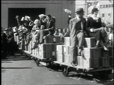 cargo of alcohol is unloaded from the freighter dorothy luckenbach / people riding a train of carts piled with cases of imported liquor celebrating... - 禁酒法点の映像素材/bロール