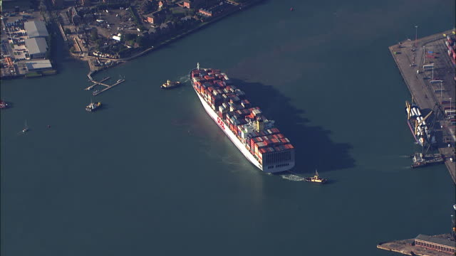 aerial cargo ship and tugboats at southampton port / hampshire, united kingdom - southampton hampshire stock-videos und b-roll-filmmaterial