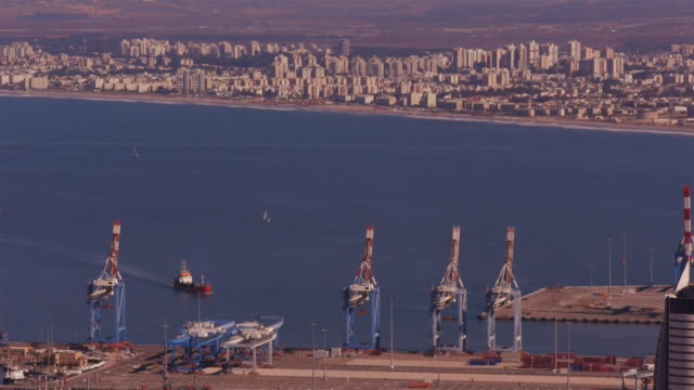 cargo ship approaching the commercial harbor of haifa - seen from above - spoonfilm stock-videos und b-roll-filmmaterial