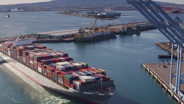 Cargo Ship Arriving Into Dock Beneath Line of Cranes