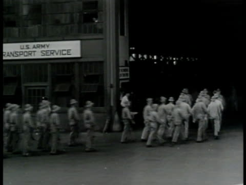vídeos de stock, filmes e b-roll de cargo ship at dock men walking into us army transport service warehouse vs loading ship w/ crane supplies in net metal cylinder boxes into cargo hold... - 1943