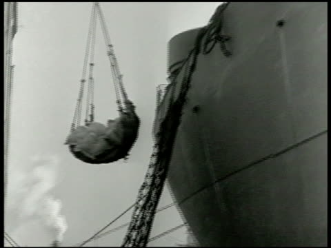 cargo ship at dock ship being loaded cu label of origin in french arabic packages lowered into cargo hold of ship cu crate of refined lard wwii world... - ausgemergelt stock-videos und b-roll-filmmaterial