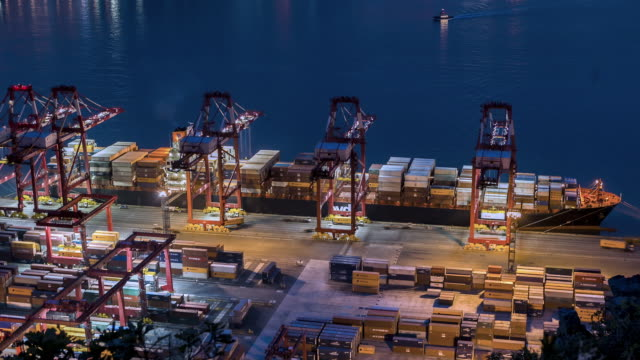 TL, MS, HA A cargo ship being unloaded by cranes at a busy port / Busan, South Korea